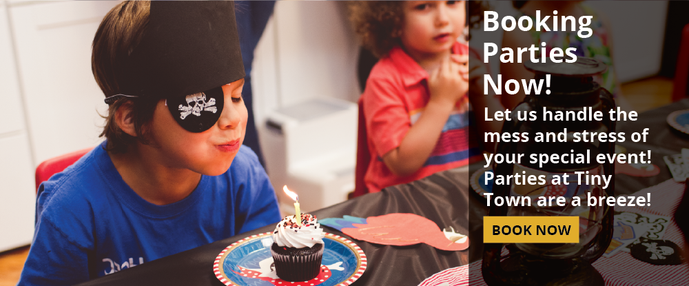 """Photo of a child in a pirate costume blowing out a candle on a cupcake at a party. The words """"Booking Parties Now! Let us handle the mess and stress of your special event! Parties at Tiny Town are a breeze!"""" are overlaid."""